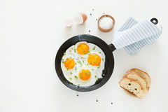 Fried scrambled eggs in a frying pan, bread and salt on a white background. Royalty Free Stock Photography