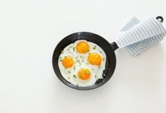 Fried scrambled eggs in a frying pan, bread and salt on a white background. Stock Image