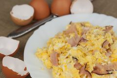 Fried scrambled eggs on a plate. Hearty meals for athletes. Diet Food. Traditional breakfast on the table. Domestic eggs. Stock Photos
