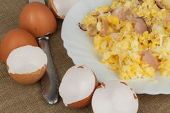 Fried scrambled eggs on a plate. Hearty meals for athletes. Diet Food. Traditional breakfast on the table. Domestic eggs. Royalty Free Stock Image