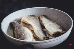 Fried sea bass fish. With golden crisp skin in a frying pan royalty free stock photo