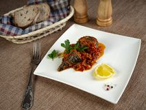 Fried sea bass. Roasted sea bass with beur Noir sauce and caramelized lemon royalty free stock photography