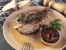 Fried sea bass. Roasted sea bass with beur Noir sauce and caramelized lemon stock photos