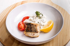 Fried sea hake fillet with creamy potato puree, tomato slices an Stock Photo