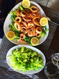 Fried seafood on bed of lettuce leafs. Fried seafood calamari and shrimp on bed of lettuce leafs, local dish, Palermo, Sicily, Italy Stock Photos