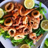 Fried seafood on bed of lettuce leafs. Fried seafood calamari and shrimp on bed of lettuce leafs, local dish, Palermo, Sicily, Italy Stock Photo