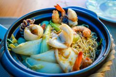 Fried seafood with pasta and fresh vegetables royalty free stock photo