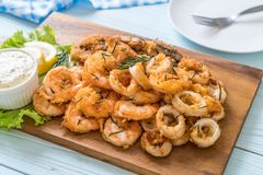 fried seafood (squids, shrimps, mussels) with sauce Royalty Free Stock Images