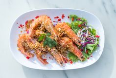 Fried shrimp with garlic pepper. In a plate garnished with green vegetables. And chili Stock Image