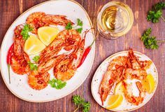 Fried shrimp with lemon and white wine. On a dark wooden background Stock Photos