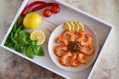 Fried shrimp on a platter, fragrant Basil,  lemons, hot peppers, tomatoes on a beautiful tray. stock images