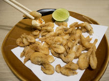 Fried shrimps with chopsticks. Japanese styled fried shrimps with a sliced lime in the brown ceramic plate with the chopsticks Stock Photos