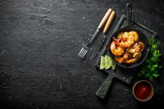 Fried shrimps in a frying pan on a cutting Board with sauce, parsley and slices of lime stock photography