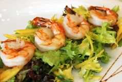 Fried shrimps with greens. Appetizing tails of fried shrimp with greens. Restaurant menu. Delicious seafood. A salad with king prawns stock image