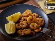 Fried shrimps and lemon in a black plate. With glass of beer on dark background. Close up royalty free stock photography