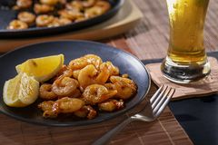 Fried shrimps and lemon in a black plate with glass of beer on dark background. stock image