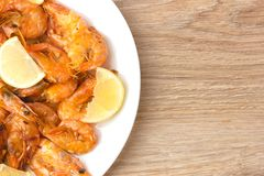 Fried shrimps with lemon. Shrimp fried in a frying pan with butter and garlic Royalty Free Stock Photography