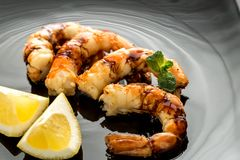 Fried shrimps with lemon wedges on the black background Stock Photography
