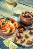 Fried shrimps and mussels with glass of white wine Stock Photos