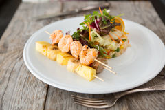 Fried shrimps skewer. Grilled shrimps, pineapples skewer with rice and vegetables royalty free stock image