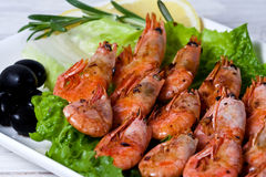 Fried shrimps with spices, olives and a lemon Royalty Free Stock Photo