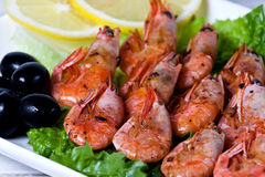 Fried shrimps with spices, olives and a lemon Stock Images