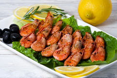 Fried shrimps with spices, olives and a lemon Royalty Free Stock Image