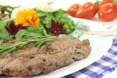 Fried Sirloin steak with wild herb salad. On a light background stock images