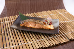Fried slice of salmon. Fried slice salmon on a black plate Royalty Free Stock Images