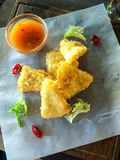 Fried slices of deep-fried cheese, hot sauce stock images