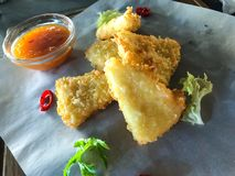 Fried slices of deep-fried cheese, hot sauce stock image