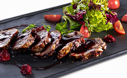 Fried slices of veal with salad close-up. Roasted slices of veal seasoned with cherry sauce and salad on white table stock images