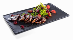 Fried slices of veal with salad mix isolated. Roasted slices of veal seasoned with cherry sauce and salad on black mat square plate on white table stock images