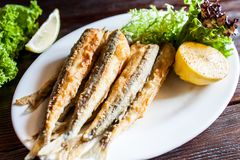 Fried small capelin on a plate on a wooden table. A good beer snack. stock photos