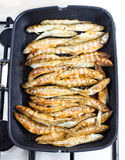 Fried small smelt fish on a barbecue grill  hotplate Stock Photo