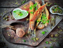 Fried smelts with sauce on a wooden Board Royalty Free Stock Photos