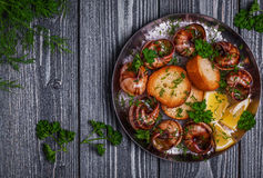 Fried snails with garlic butter and herbs on dark background Stock Photos