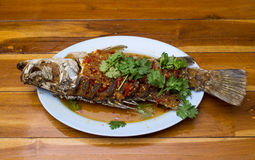 Fried snapper with chili sauce on the plate with wood table Stock Photos
