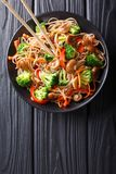 Fried soba noodles with mushrooms, broccoli, carrots, peppers cl. Oseup on a plate on a table. Vertical top view from above stock photography