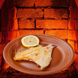 Fried sole fish on plate and hot bricks of oven Stock Image