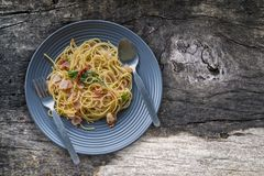 Fried spaghetti with bacon on plate on old wooden board. stock photo