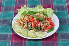 Fried spicy basil with minced pork topped sliced green lemon and and lettuce. Royalty Free Stock Image