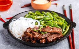 Fried spicy beef with sesame seeds, green beans and rice noodles. Dinner in the Asian style. Selective focus royalty free stock images