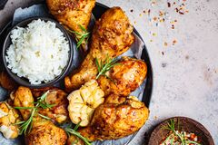 Baked spicy chicken legs with rice, garlic and herbs in black plate, dark background, top view