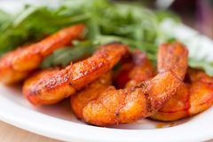 Fried spicy shrimp, prawn and salad of arugula Royalty Free Stock Photos