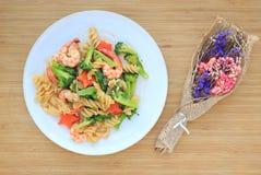 Fried Spiral Macaroni met garnalen en groenten met droge bloem op houten achtergrond worden verfraaid die stock afbeelding