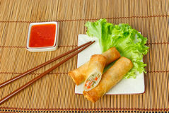 Fried spring rolls, one cut, on a plate with chopsticks Royalty Free Stock Photography