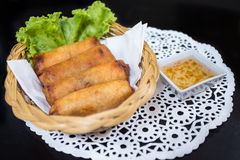 Fried Spring Rolls (Por Pia Tod). With sweet syrup sauce on black table Stock Image