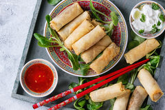 Fried spring rolls with sauce. Fried spring rolls with red and white sauces, served in china plate on wood tray with fresh green salad and wooden chopsticks over Stock Photography