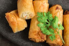 Fried Spring Rolls Stacked on black slate plate on wooden Royalty Free Stock Images